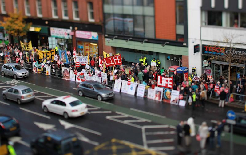 "Police stand at the entrance of the Marie Stopes clinic as anti abortion protestors hold up placards outside the first private clinic to offer abortions to women in Belfast, Northern Ireland on October 18, 2012. Dozens of pro-life campaigners protested outside the first abortion clinic in Northern Ireland as it opened to the public. Around 50 protesters brandishing placards saying ""Life is precious"" and showing photographs of foetuses gathered outside the privately run clinic in an anonymous building in Belfast. AFP PHOTO/ Peter Muhly -NOTE TO EDITORS THIS PICTURE WAS TAKEN USING A TILT AND SHIFT LENS - (Photo credit should read PETER MUHLY/AFP via Getty Images)"