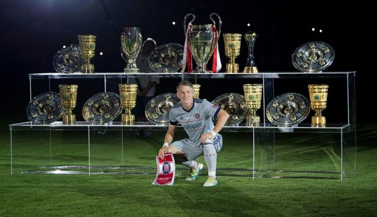 Former Germany captain and Chicago Fire midfielder Bastian Schweinsteiger poses in front of some of the trophies he won during his 17-year career with Bayern Munich, who he joined as a 13-year-old in 2002 before leaving in 2015 for Manchester United