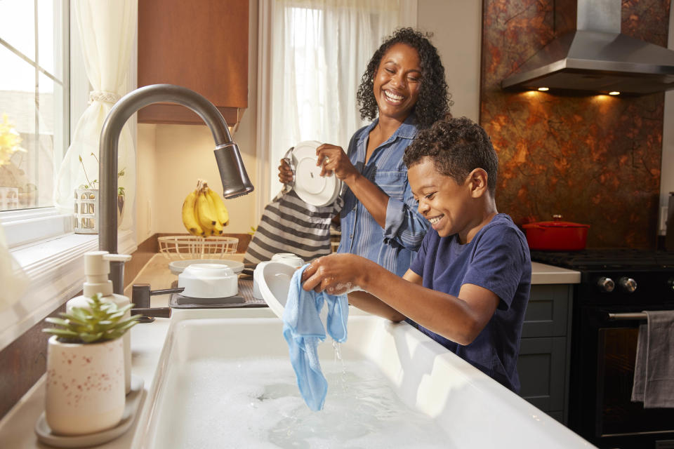 Mother and child washing dishes together in kitchen, sharing chores