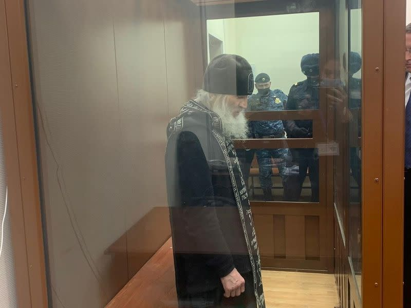 Father Sergiy Romanov, a coronavirus-denying priest suspended by the Russian Orthodox Church for disobeying orders, stands inside a defendants' cage during a court hearing in Moscow