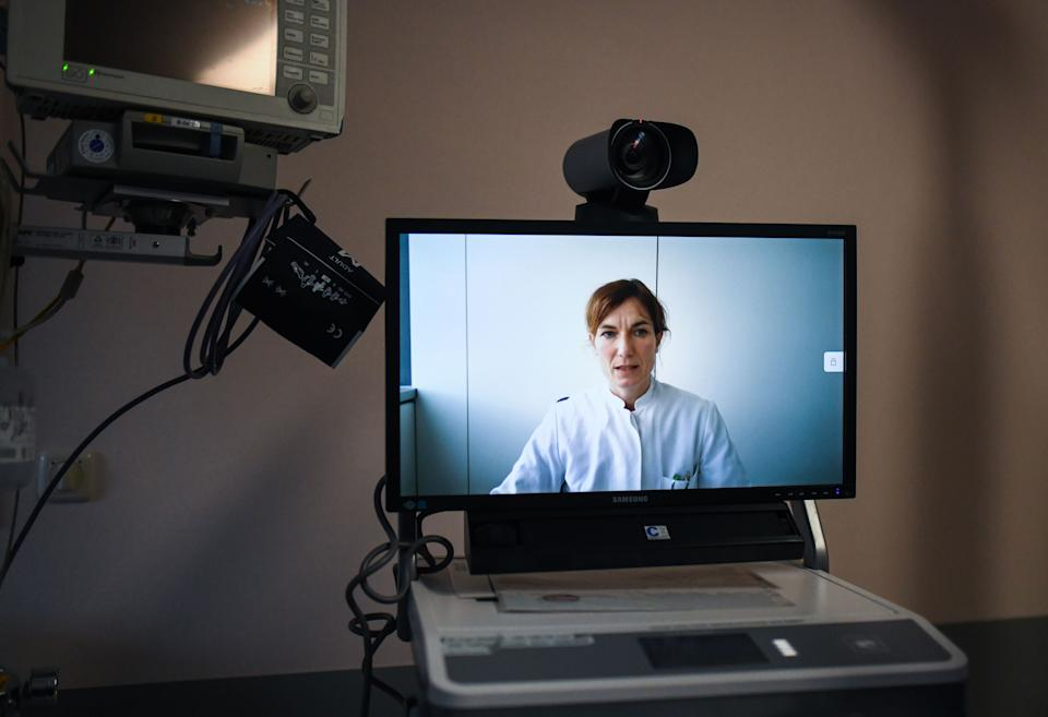A monitor shows intensive care physician Judith Ibba at the University hospital in Aachen as she speaks during an online meeting about a COVID-19 case while using telemedicine on January 26, 2021 at the Bethlehem Hospital in Stolberg, western Germany, amid the ongoing coronavirus pandemic. - To discuss the most serious Covid-19 cases, Andreas Bootsveld is not alone. In addition to colleagues in his intensive care unit, he can draw on the advice of several experts. However, this panel of specialists is not on the clinic premises, but some 20 kilometres away. Telemedicine, which is carried out via videoconference visits, is accelerating with the pandemic. (Photo by Ina FASSBENDER / AFP) (Photo by INA FASSBENDER/AFP via Getty Images)
