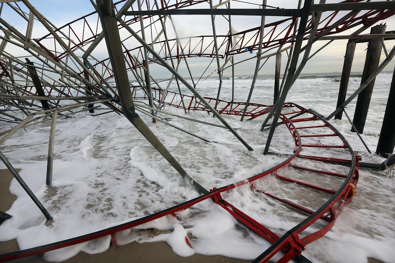 SEASIDE HEIGHTS, NJ - NOVEMBER 16:   Waves break at a destroyed roller coaster from the Funtime Pier on November 16, 2012 in Seaside Heights, New Jersey. Two amusement piers and a number of roller coasters in the seaside town were destroyed by Superstorm Sandy.  (Photo by Mario Tama/Getty Images)