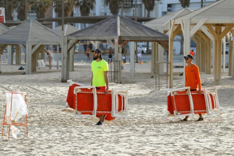 Beach-workers lay out lounge chairs on a beach in Tel Aviv (AFP Photo/JACK GUEZ)