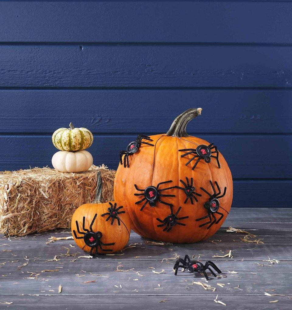 <p>Creepy spider made from buttons, string, and pipe cleaners slither about pumpkins. The very idea is sure to make your skin crawl!<strong><br></strong></p><p><strong>Make the pumpkin</strong>: Thread red string through the holes of a large or medium-size black button in a crisscross pattern; knot or glue in the back to hold in place. Cut eight 1- to 2-inch lengths of black pipe cleaner and glue to the back of the button with hot glue with four on each side; shape into legs. Attach a smaller black button with hot-glue to make a head. Repeat as desired. Attach a black string to the back of the larger button with hot-glue, and hang spider around stem or attach directly to a pumpkin with hot-glue. </p>