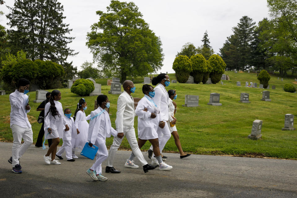 """The family of Joanne Paylor, 62, of Washington, walks through Lincoln Memorial Cemetery for her interment ceremony, in Suitland-Silver Hill, Md., Sunday, May 3, 2020. From right are her children, Colletta Paylor, Iran """"Bang"""" Paylor, and LaShawn Paylor, followed by several of her grandchildren. Paylor's funeral was delayed for almost two months while her family hoped social distancing guidelines would be lifted. Despite not having died from coronavirus, almost every aspect of her funeral has been impacted by the pandemic. (AP Photo/Jacquelyn Martin)"""