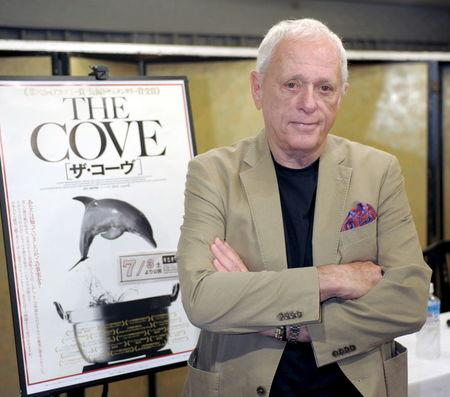 """Ric O'Barry, a U.S. dolphin conservationist who appeared in the Oscar-winning documentary """"The Cove"""", poses with a poster of his film before a news conference in Osaka, western Japan, in this Kyodo picture taken June 12, 2010. REUTERS/Kyodo/Files"""
