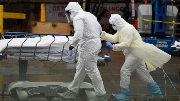 PHOTO: In this April 9, 2020, file photo, medical personnel move a deceased patient to a refrigerated truck serving as make shift morgues at Brooklyn Hospital Center in New York. (Angela Weiss/AFP via Getty Images, FILE)