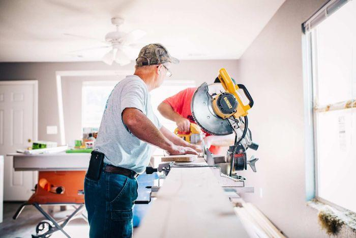 Two tradesmen cutting a long piece of timber in a living room