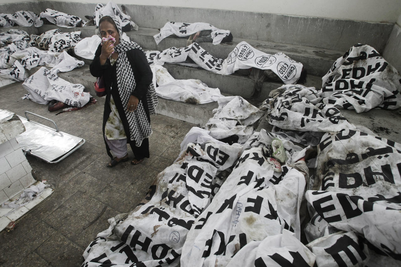 A woman looks for her missing family member at a morgue in Karachi, Pakistan, Wednesday, Sept. 12, 2012. Pakistani officials say the death toll from devastating factory fires that broke out in two major cities has killed hundreds. (AP Photo/Fareed Khan)