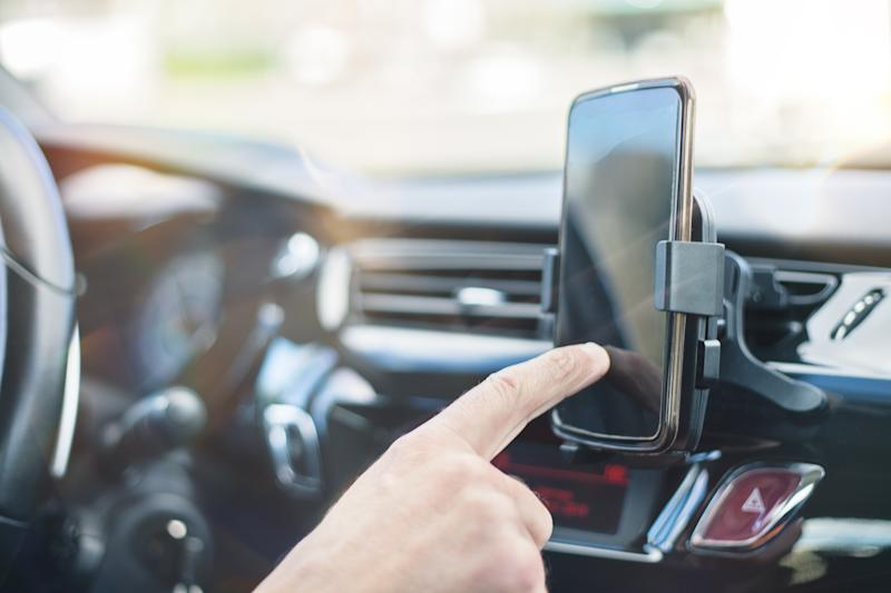 Close up of a man hand using smart phone while driving