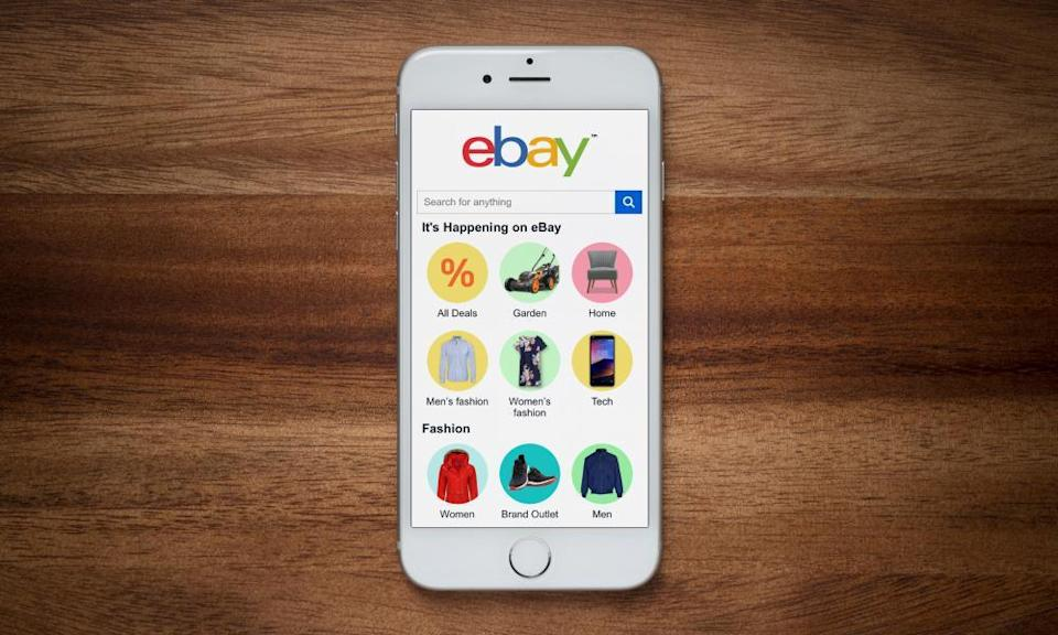 An iPhone showing the ebay website rests on a plain wooden table.