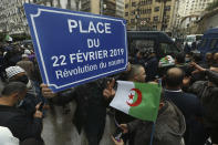 "Algerians demonstrate in Algiers, one with a plaque reading ""Square of Feb.22, 2019, the Smiling Revolution"" to mark the second anniversary of the Hirak movement, Monday Feb. 22, 2021. February 22 marks the second anniversary of Hirak, the popular movement that led to the fall of Algerian President Abdelaziz Bouteflika. (AP Photo/Anis Belghoul)"