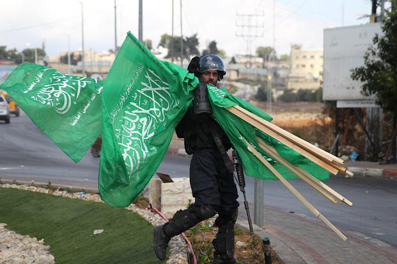 An Israeli soldier carries seized Hamas flags in Beit El Jewish settlement north of Ramallah, on October 8, 2015