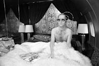<p>Elton John in bed on board a private jet in 1975. </p>