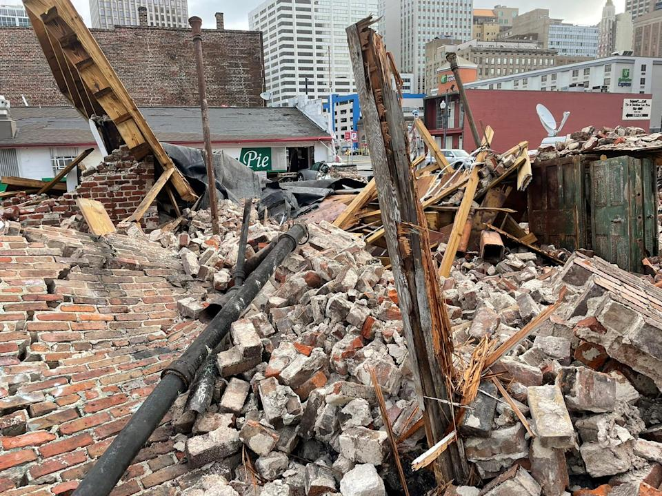 Pile of bricks, metal pipe, and wood from a building collapse.