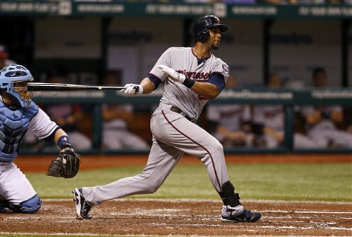 Minnesota Twins' Aaron Hicks follows through on a double in front of Tampa Bay Rays catcher Jose Molina during the fifth inning of a baseball game on Wednesday, July 10, 2013, in St. Petersburg, Fla. (AP Photo/Mike Carlson)