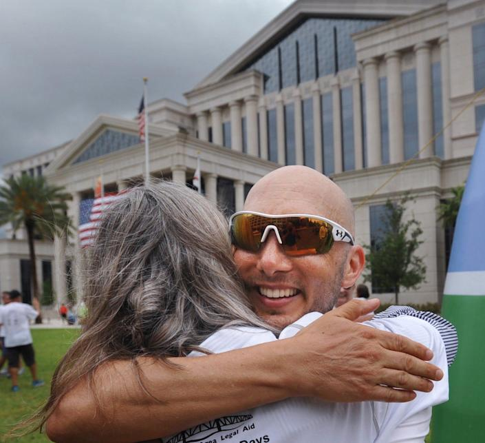 Attorney Mike Freed, being hugged in this 2017 photo after finishing a six-day run from Tallahassee to raise money for Jacksonville Area Legal Aid, is using his role with a national legal organization to urge attorneys to donate time working with renters and landlords to try to resolve a backlog of pandemic-driven rent disputes without mass evictions.