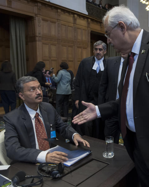 Pakistan's attorney general Anwar Mansoor Khan, right, greets Deepak Mittal, the joint secretary of India's Foreign Ministry, prior to India presenting oral arguments at the International Court of Justice, or World Court, in The Hague, Netherlands, Monday, Feb. 18, 2019. India is taking Pakistan to the United Nations' highest court in an attempt to save the life of an Indian naval officer sentenced to death last month by a Pakistani military court after being convicted of espionage.(AP Photo/Peter Dejong)