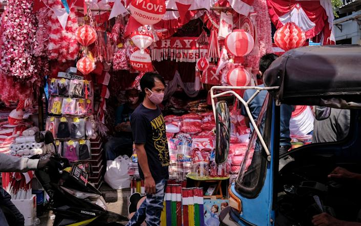 Mandatory Credit: Photo by MAST IRHAM/EPA-EFE/Shutterstock (10726181e) People wear face masks at a market amid the coronavirus pandemic in Jakarta, Indonesia, 29 July 2020. The national COVID-19 task force has classified Jakarta as a 'red zone', a high risk area for COVID-19. Indonesia has recorded over 100,000 cases of COVID-19, the highest in Southeast Asia. Coronavirus in Jakarta, Indonesia - 29 Jul 2020 - Shutterstock