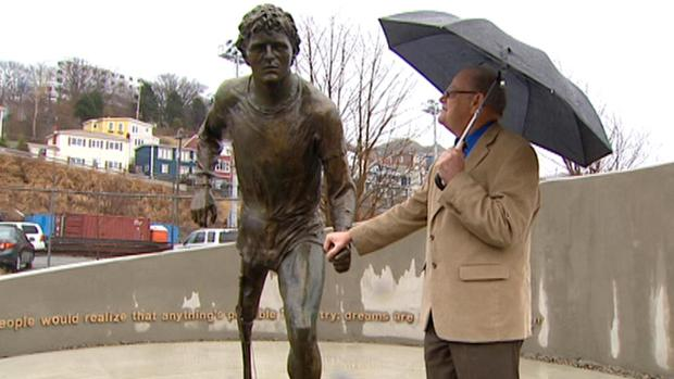 Rolly Fox holds the hand on a statue of his son, Terry Fox, soon after its unveiling in St. John's on Thursday.