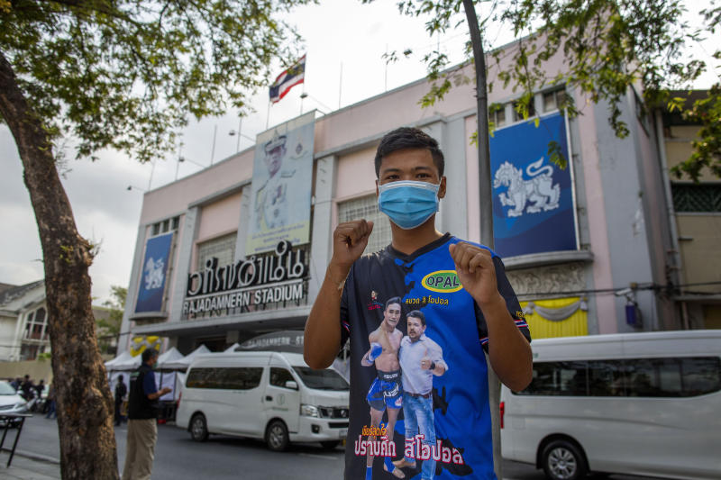 In this Thursday, March 19, 2020 photo, a Muay Thai boxing fighter poses for a photo in front of a makeshift screening facility outside Rajadamnern boxing stadium in Bangkok, Thailand. Kickboxing aficionados came from all over Thailand to attend a major Muay Thai tournament at Bangkok's indoor Lumpini Stadium on March 6, 2020. Dozens or more went home unknowingly carrying the coronavirus. For most people the new COVID-19 coronavirus causes only mild or moderate symptoms, but for some it can cause more severe illness. (AP Photo/Gemunu Amarasinghe)