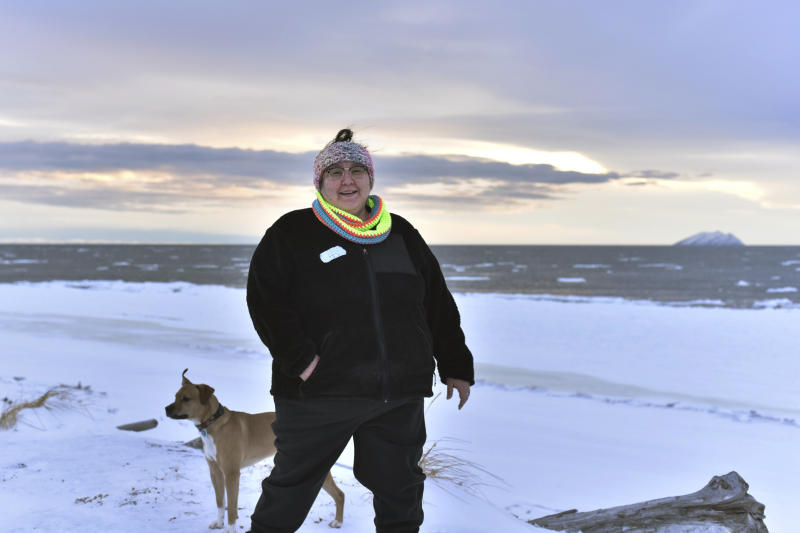 """In this Jan. 14, 2019 photo, Clarice """"Bun"""" Hardy stands on the beach with her dog, Marley, in the Native Village of Shaktoolik, Alaska. Hardy, a former 911 dispatcher for the Nome Police Department, says she moved back to her village after a sexual assault left her feeling unsafe in Nome. (AP Photo/Victoria Mckenzie)"""