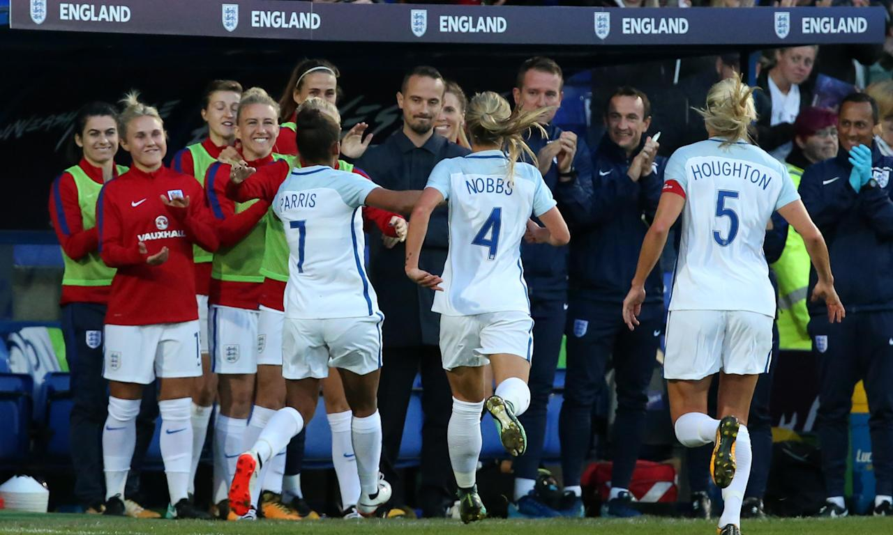 England players rush to celebrate their first goal with their manager, Mark Sampson, during the 6-0 win over Russia at Prenton Park on Tuesday night.