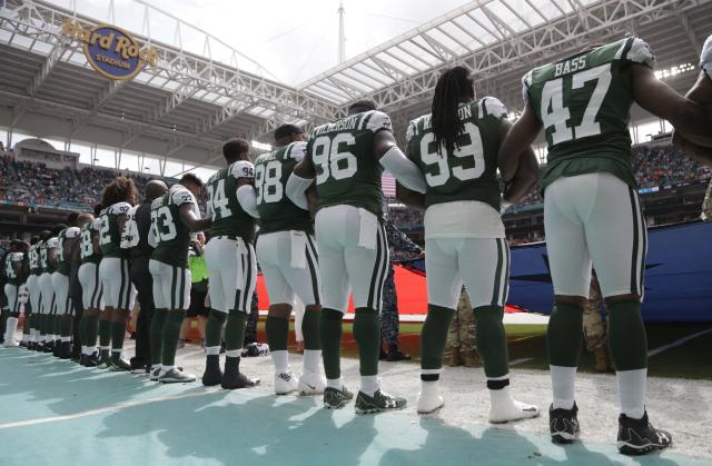 The Jets hold hands during the national anthem in Miami. (AP)