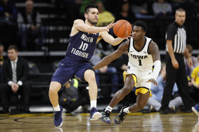 North Florida guard Ivan Gandia-Rosa (10) passes in front of Iowa guard Joe Toussaint (1) during the first half of an NCAA college basketball game, Thursday, Nov. 21, 2019, in Iowa City, Iowa. (AP Photo/Charlie Neibergall)