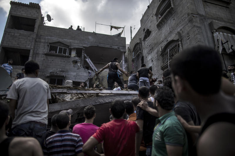 Palestinian men gather around the rubble of a house to look for survivors after it was hit by an Israeli air strike on the al-Shati refugee camp in Gaza City on August 4, 2014 (AFP Photo/Marco Longari )