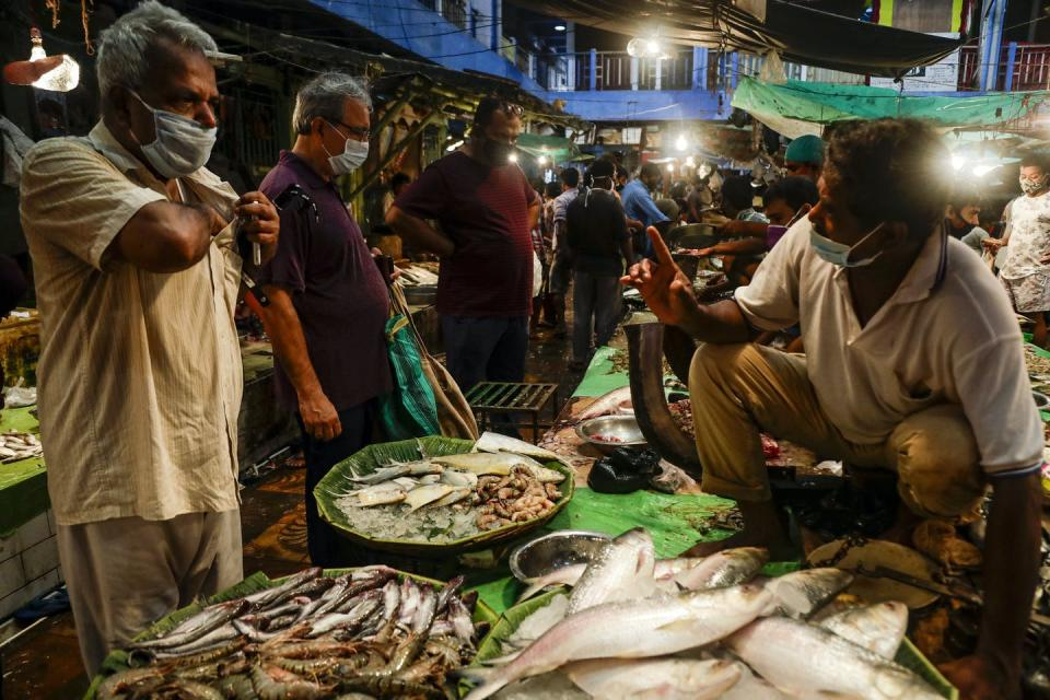 A man buying fish from another man at a market.