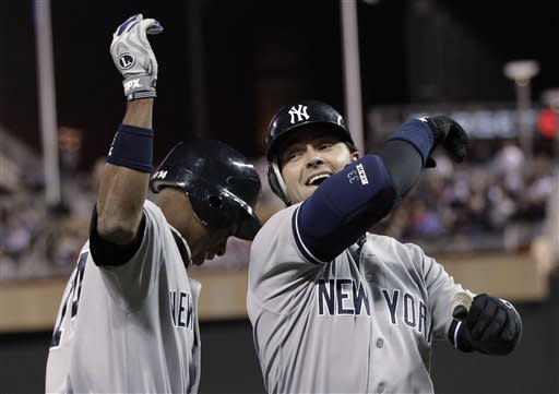 New York Yankees' Curtis Granderson, left, and Nick Swisher celebrate Swisher's two-run home run off Minnesota Twins pitcher Esmerling Vasquez in the fourth inning of a baseball game Tuesday, Sept. 25, 2012, in Minneapolis. (AP Photo/Jim Mone)