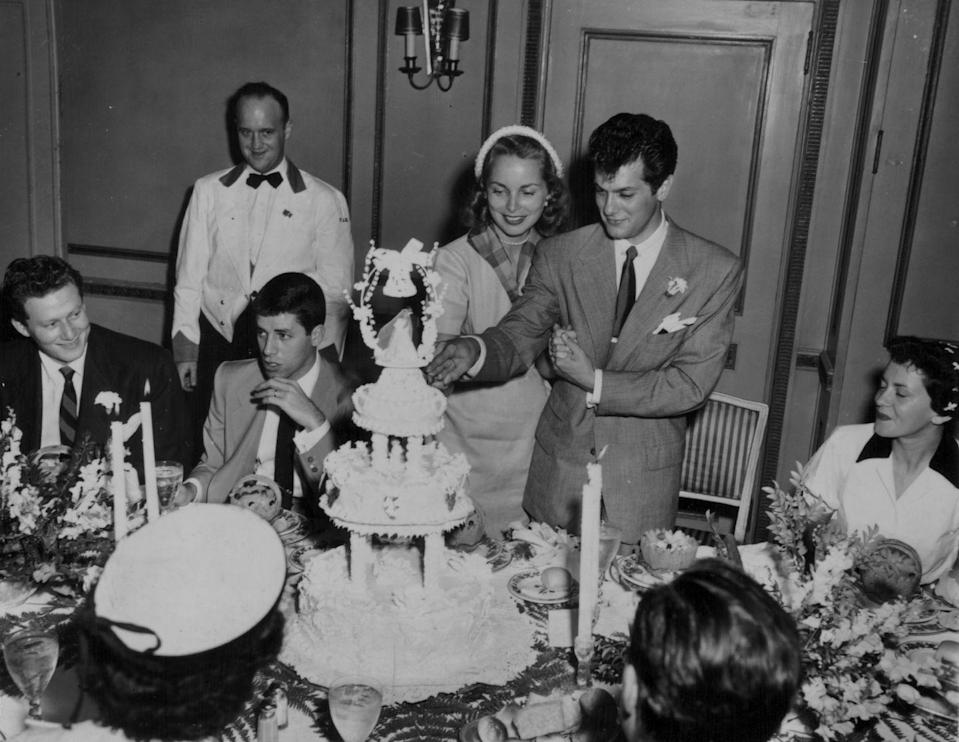 "<p>Arguably the ""it couple"" of the 1950s, Janet Leigh and Tony Curtis' 1951 nuptials (with Jerry Lewis as the best man!) marked a classic Hollywood moment. The duo celebrated their small wedding with a tiered wedding cake and large floral centerpieces.</p>"