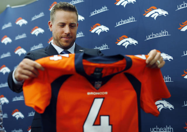 Case Keenum looks over his new jersey during a NFL football news conference introducing him as the new starting quarterback of the Denver Broncos, Friday, March 16, 2018, at the team's headquarters in Englewood, Colo. (AP Photo/David Zalubowski)