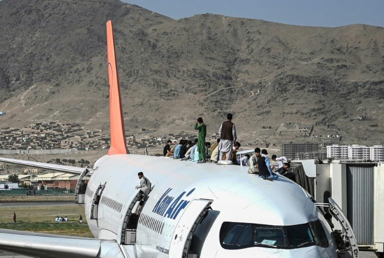 Afghans climb atop a plane at the Kabul airport on August 16, 2021, as hundreds of people mobbed the facility, clinging to planes even as they taxiied down the runway in an attempt to flee Taliban rule