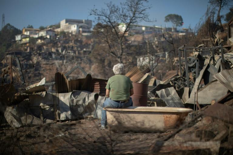 A man looks at the destruction caused by a forest fire on Rocuant hill in Valparaiso, Chile, on December 25, 2019 (AFP Photo/Pablo Rojas Maradiaga)