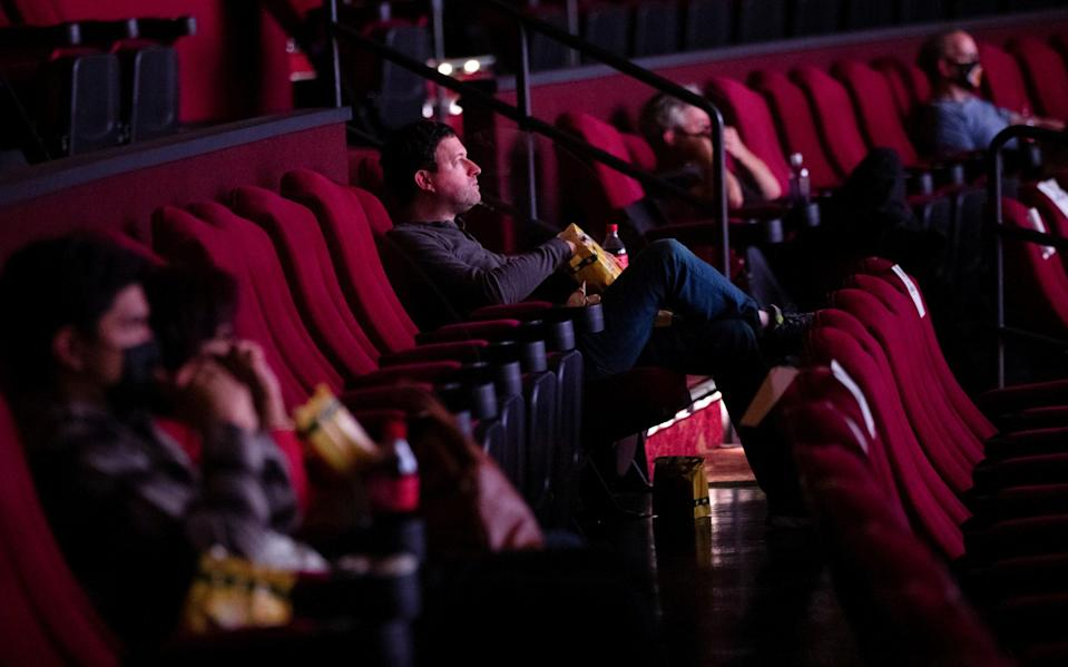 "Moviegoers sit socially distanced as they wait for the movie ""Godzilla vs. Kong"" on reopening day of the TCL Chinese theatre during the outbreak of the coronavirus disease (COVID-19), in Los Angeles - MARIO ANZUONI/REUTERS"