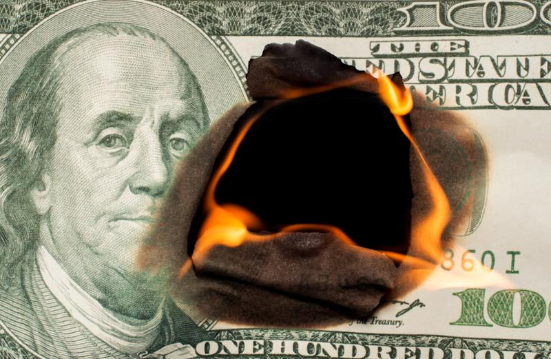 A one hundred dollar bill burning from the inside outward.
