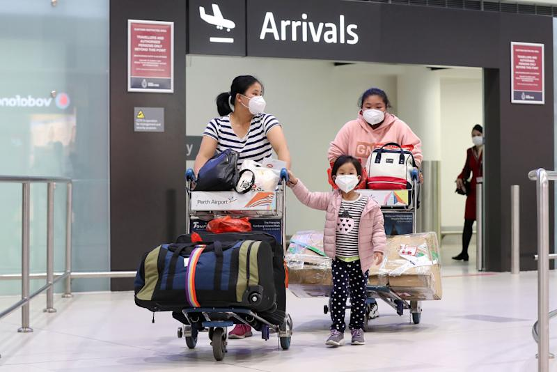 Travel restrictions have been tightened further for inbound international travellers. A family wearing masks arrive in Perth. Source: Getty