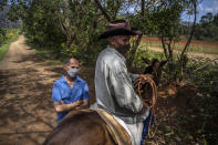 Luis Orlando Deulofeu, who owns the MogoteArt Hostel, poses for a portrait behind a passing horse rider outside his hotel in Viñales, Cuba, March 1, 2021. Both U.S. sanctions meant to punish the government and a COVID-19 pandemic have squashed tourism almost everywhere, making some Cubans hope that new U.S. President Joe Biden will reverse at least some of the restrictions implemented by his predecessor. (AP Photo/Ramon Espinosa)
