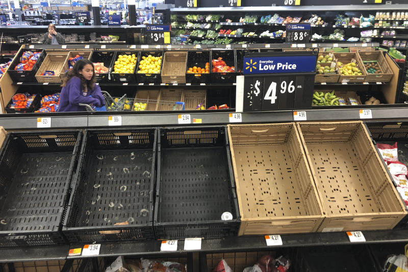 Display baskets are nearly empty in the produce section of a Walmart in Warrington, Pa., Tuesday, March 17, 2020. Concerns over the new coronavirus have led to consumer panic buying of grocery staples in stores across the country. (AP Photo/Matt Rourke)