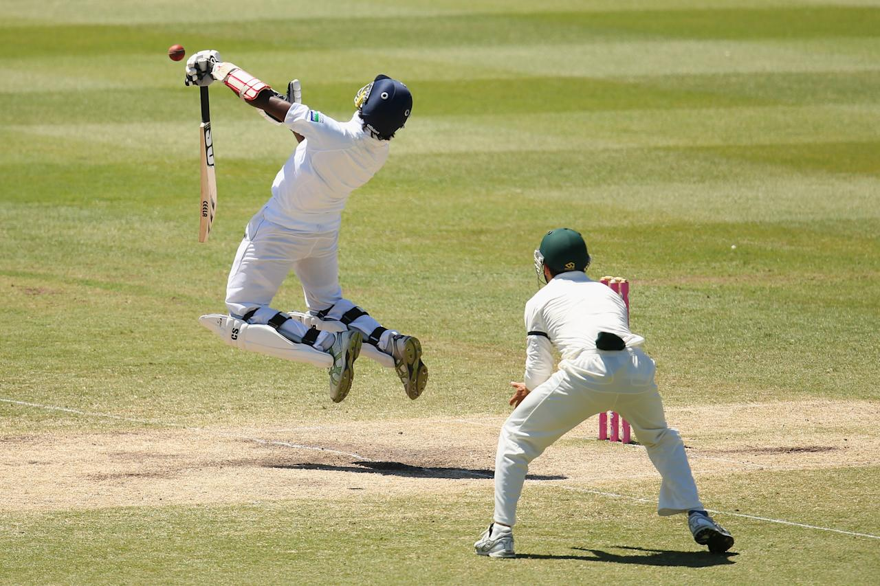 SYDNEY, AUSTRALIA - JANUARY 06: Nuwan Pradeep of Sri Lanka fends off a delivery by Mitchell Johnson of Australia during day four of the Third Test match between Australia and Sri Lanka at Sydney Cricket Ground on January 6, 2013 in Sydney, Australia.  (Photo by Cameron Spencer/Getty Images)
