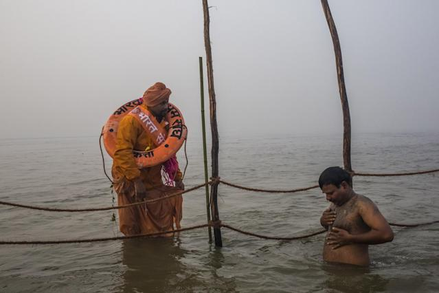 ALLAHABAD, INDIA - JANUARY 14: A Hindu lifesaver keeps a watchfull eye as devotees bathe in the waters of the holy Ganges river during the auspicious bathing day of Makar Sankranti of the Maha Kumbh Mela on January 14, 2013 in Allahabad, India. The Maha Kumbh Mela, believed to be the largest religious gathering on earth is held every 12 years on the banks of Sangam, the confluence of the holy rivers Ganga, Yamuna and the mythical Saraswati. The Kumbh Mela alternates between the cities of Nasik, Allahabad, Ujjain and Haridwar every three years. The Maha Kumbh Mela celebrated at the holy site of Sangam in Allahabad, is the largest and holiest, celebrated over 55 days, it is expected to attract over 100 million people. (Photo by Daniel Berehulak/Getty Images)