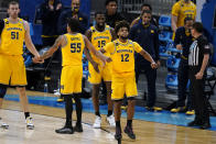 Michigan guard Mike Smith (12) celebrates with teammates during the second half of a Sweet 16 game against Florida State in the NCAA men's college basketball tournament at Bankers Life Fieldhouse, Sunday, March 28, 2021, in Indianapolis. (AP Photo/Jeff Roberson)