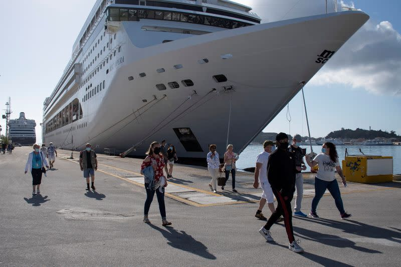 Passengers of the Costa Luminosa cruise ship wearing protective face masks make their way at the port of the island of Corfu