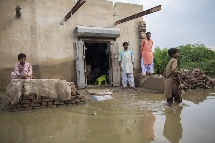People stand outside a flooded property in one of the worst-hit areasSaiyna Bashir/Arete/WFP Asia
