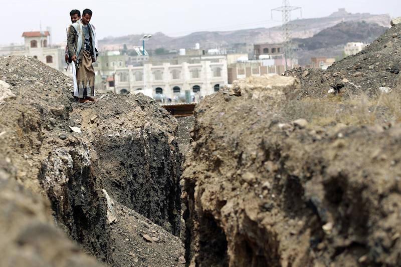 Armed Yemeni Shiite Huthi rebels stand next to a trench at the Al-Iman Islamic University which they captured in the Yemeni capital, Sanaa on September 29, 2014 (AFP Photo/Mohammed Huwais)