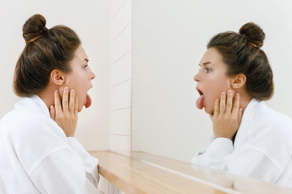 Young woman is looking on her tongue in the mirror