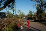 Iyana Sells, 9, plays on her street which is still lined with debris from Hurricane Laura the day after Hurricane Delta swept through Lake Charles