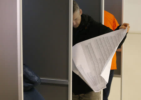 A voter studies a list of candidates for the general election in The Hague. REUTERS/Michael Kooren